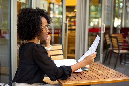 casual business: young woman at the coffee shop reading a document Stock Photo