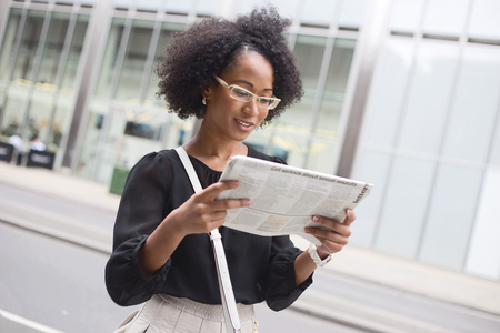 american media: young office woman reading the newspaper in the street