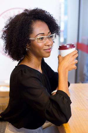 shop window: young woman enjoying a fresh cup of coffee