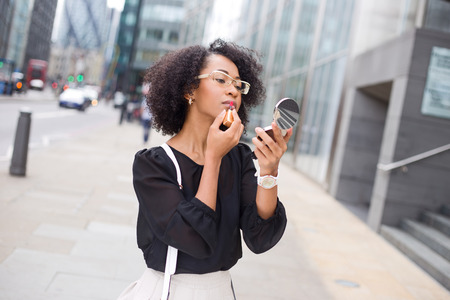 business woman apllying lipstick in the street