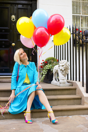 doorstep: colourful young woman with balloons sitting on a doorstep Stock Photo