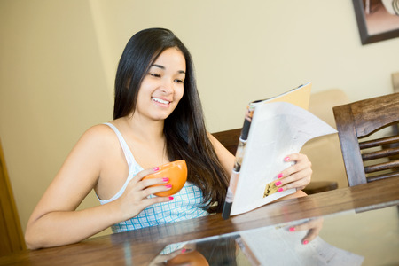 refreshment: young woman reading a magazine with a coffee in the morning