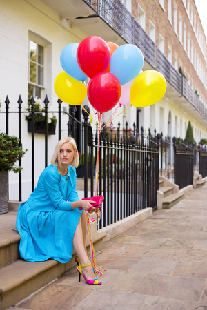 doorstep: young woman sitting on a doorstep with balloons