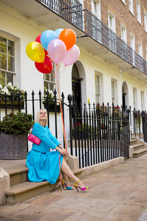 stoep: young woman sitting on a doorstep with balloons