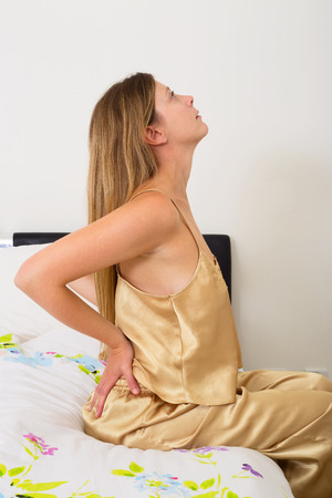 slipped: young woman feeling the pain in her back Stock Photo