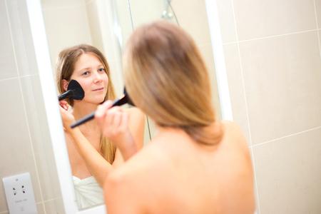mujer maquillandose: mujer joven aplicar maquillaje en el ba�o