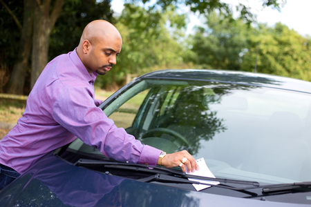 windscreen: young man leaving a message on a car windscreen
