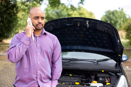 broken down: man calling the breakdown service with his car bonnet open