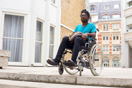 unaccessible: young man in a wheelchair at the top of steps Stock Photo