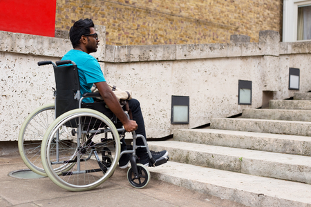 unaccessible: young man in a wheelchair waiting at the bottom of steps