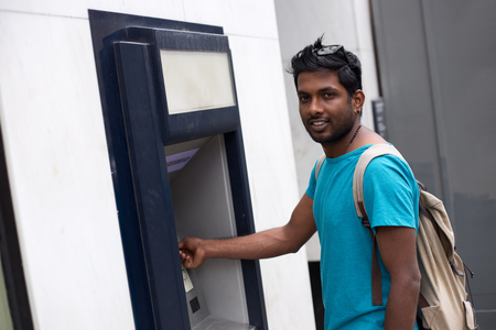 cashpoint: young man at the cash machine