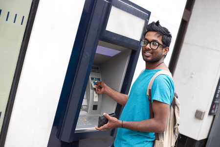 withdrawal: young indian man at the cashpoint withdrwing money