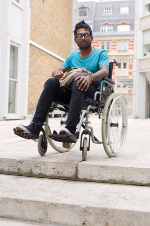unreachable: young man in a wheelchair waiting at the top of steps Stock Photo
