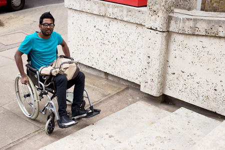 unaccessible: young man in a wheelchair at the bottom of steps