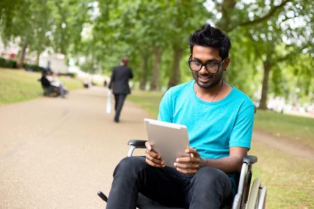 personas discapacitadas: hombre con discapacidad en el parque con un equipo Tablet PC