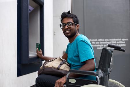 discapacitados: hombre con discapacidad en el cajero automático Foto de archivo