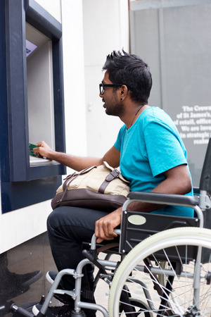 disabled man withdrawing cash at the atm Stock Photo