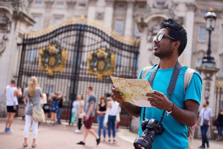 england map: Indian tourist outside buckingham palace holding a map and his camera