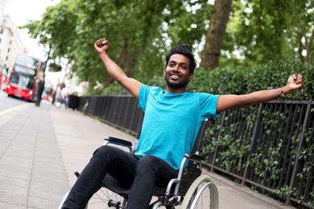 persona en silla de ruedas: hombre discapacitado en silla de ruedas que celebra