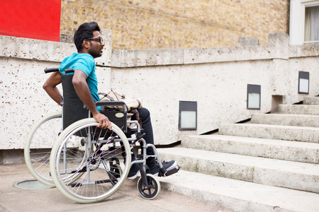 discrimination: disabled man in a wheelchair waiting at the bottom of steps