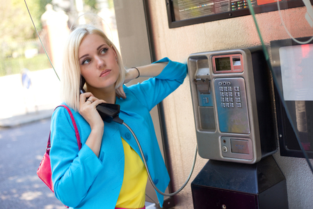 phonebooth: young colourful woman making a call at a public phone box Stock Photo