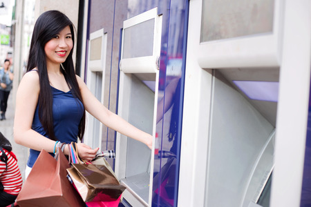 cashpoint: young japanese woman withdrawing cash from an atm while out shopping