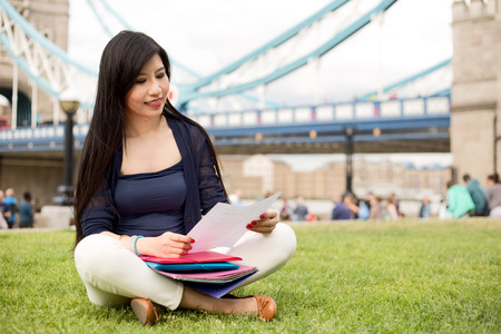 foreign secretary: Japanese student doing her paperwork by tower bridge Stock Photo