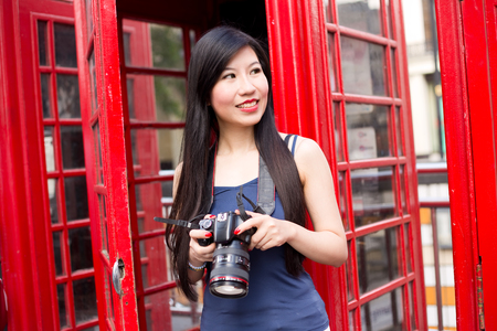 phonebox: japanese tourist in london holding her camera