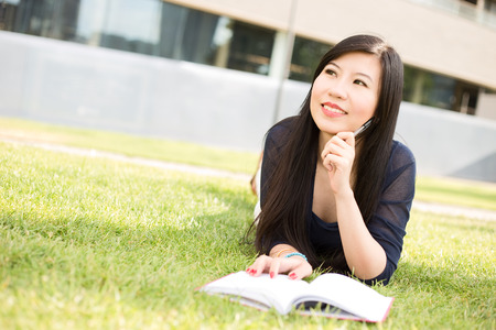 textbook: Japanese student with a textbook looking thoughtful Stock Photo