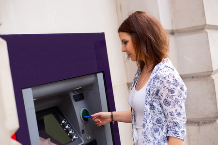 cashpoint: young woman at the cash machine
