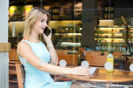coffeeshop: young woman sitting in a coffeeshop talking on the phone