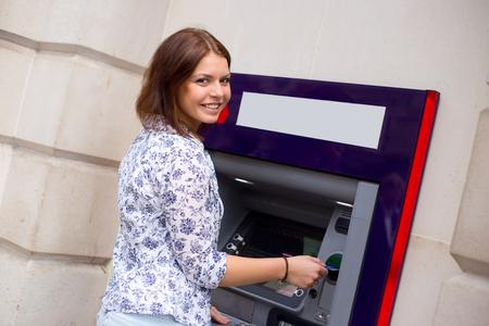 cash machine: young woman at the cash machine