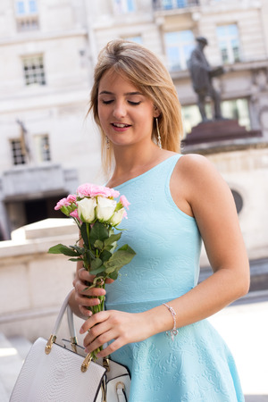 young woman in the city holding a bouquet of flowers. Stock Photo