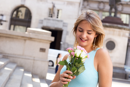 ifestyle: young woman holding a bouquet of roses in the street