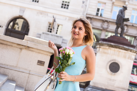 ifestyle: young woman in the street holding a bouquet of roses