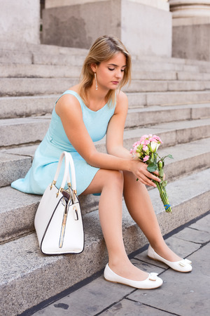 heartbroken: Sad girl sitting on steps holding a bouquet of roses.