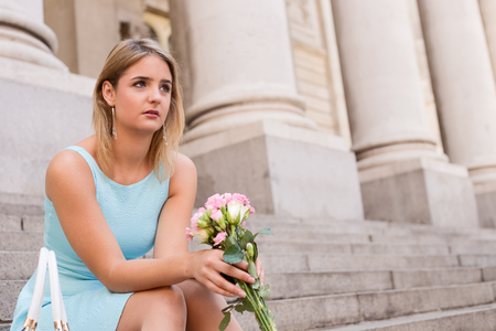 heartbroken: sad girl sitting on steps holding a bouquet of flowers