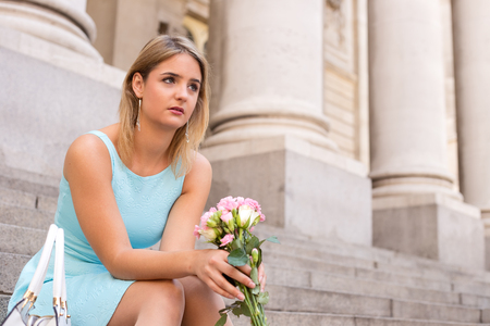 heartbroken: sad girl holding a bouquet of flowers