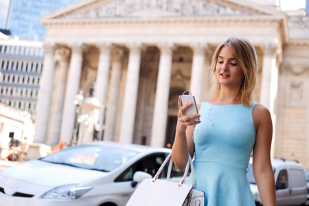 relying: young woman in the street using her mobile phone Stock Photo