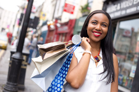 african american woman smiling: happy woman holding shopping bags