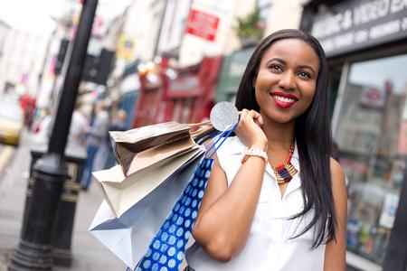 mujeres africanas: mujer feliz celebración de las bolsas de la compra