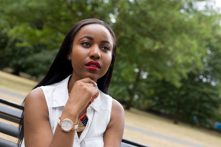 young african american woman: young woman sitting in the park thinking Stock Photo