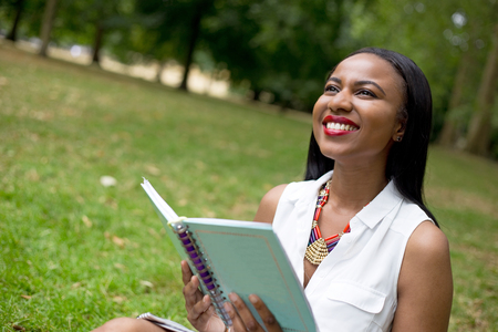 textbook: young student sitting in the park holding her textbook