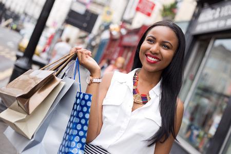 women posing: young woman holding shopping bags Stock Photo