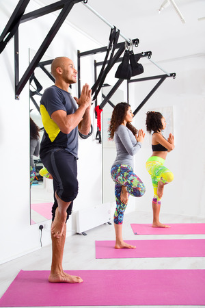 tree position: group of people at the gym practising the tree yoga pose Stock Photo