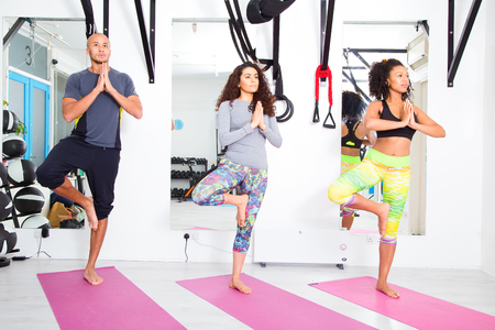 tree position: group of people at the gym practicing the tree pose