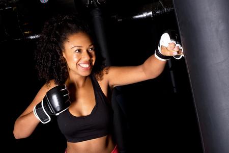 punching: young woman punching a punch bag Stock Photo