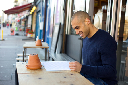 coffeeshop: young man sitting outside a coffeeshop reading a notebook