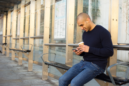 young man at the bus stop with a coffee and phone