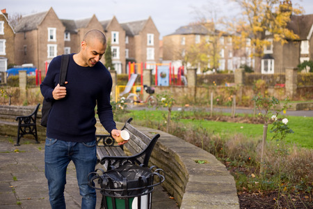 litterbin: man throwing rubbish in the bin in a park Stock Photo